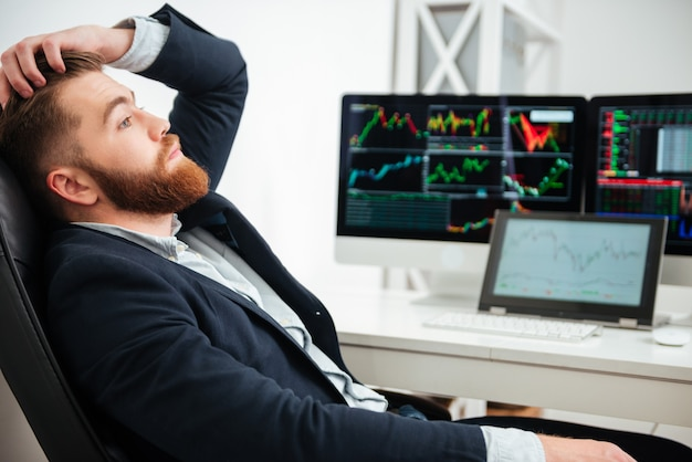 Benadrukt vermoeide jonge zakenman die zit en denkt op de werkplek op kantoor