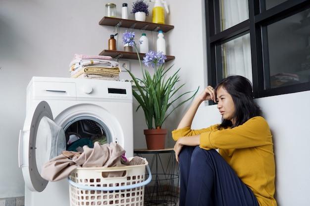 Benadrukt vrij aziatische huisvrouw die wat was thuis doet