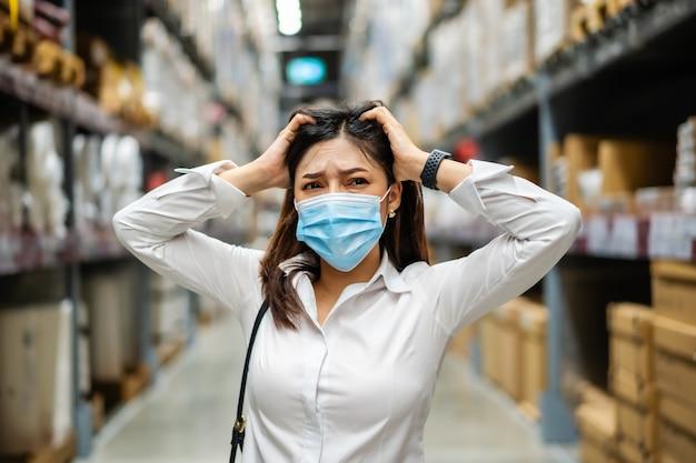 Benadrukt vrouw met medisch masker in het magazijn tijdens coronavirus-pandemie