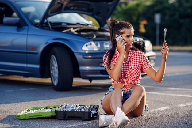 Benadrukt vrouw zit in de buurt van haar kapotte auto.