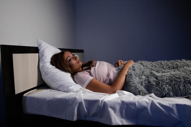 Benadrukt vrouwelijke slapeloosheid. jonge dame die in het bed ligt en wil slapen.