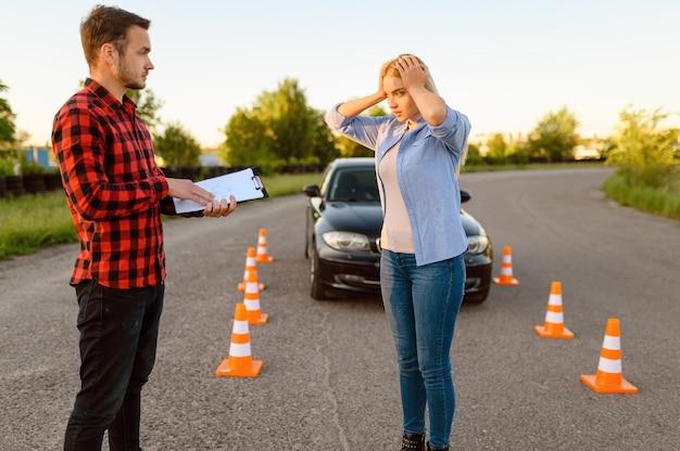 Benadrukt vrouwelijke student en instructeur met checklist op de weg, les in rijschool. man die dame leert voertuig te besturen. rijbewijs opleiding