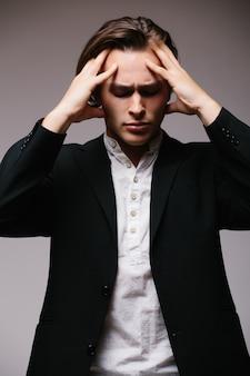 Benadrukt zakenman met hoofdpijn geïsoleerd op een grijze muur