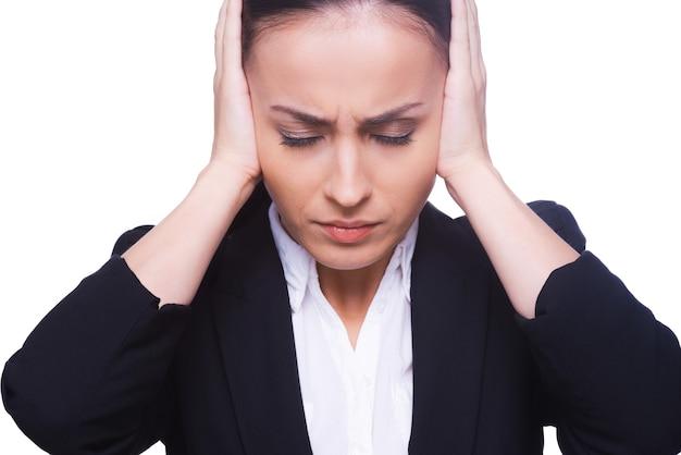 Benadrukt zakenvrouw. gefrustreerde jonge vrouw in formele kleding die oren bedekt met handen en ogen gesloten houdt terwijl ze geïsoleerd op wit staat