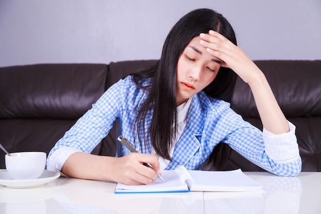Benadrukt zakenvrouw zit op haar bureau en schrijft een notitie op het notitieblok