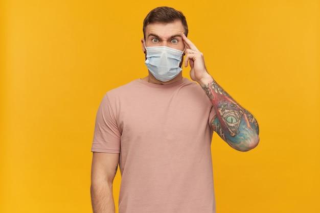 Benadrukte getatoeëerde jongeman in roze t-shirt en virusbeschermend masker op gezicht tegen coronavirus met baard die zijn slaap aanraakt en hoofdpijn heeft over gele muur