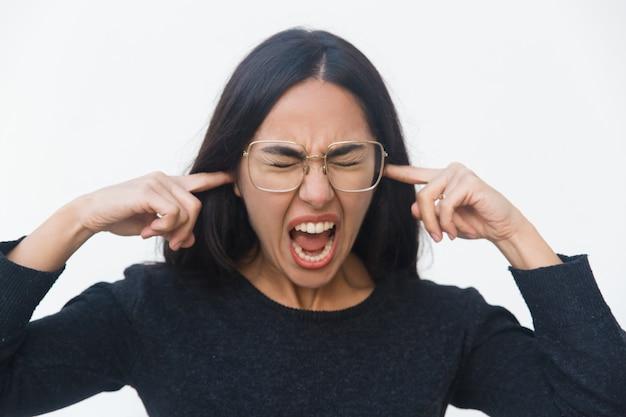 Benadrukte nerveuze vrouw die oren bedekt met handen