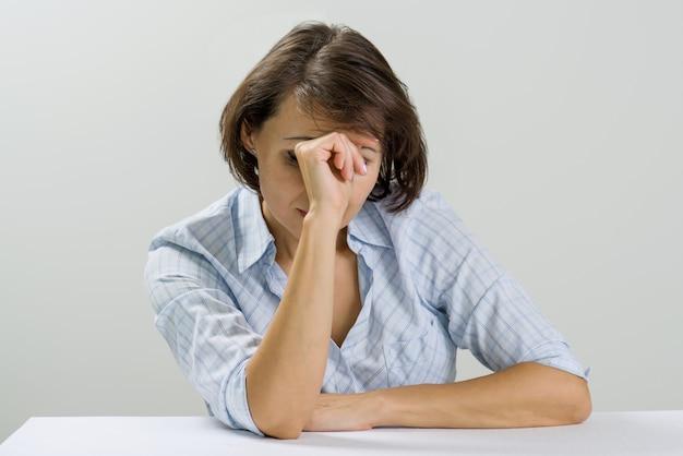 Benadrukte volwassen vrouw die haar gezicht thuis behandelt met handen.