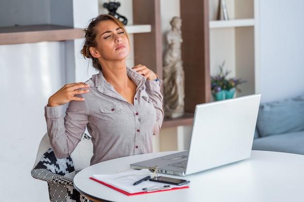 Benadrukte vrouw die aan rugpijn lijdt na het werken op pc