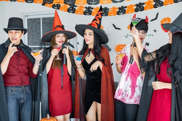 Bende van jonge aziaat in kostuumheks, tovenaar met halloweenfeest om een lied te zingen en te drinken, dessert in de kamer. groep tiener thai met vieren halloween. concept feest halloween thuis.