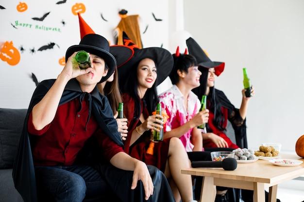 Bende van jonge aziaat in kostuumheks, tovenaar met halloweenfeest voor dans en drankje en dronken in de kamer. groep tiener thai met vieren halloween. concept feest halloween thuis.