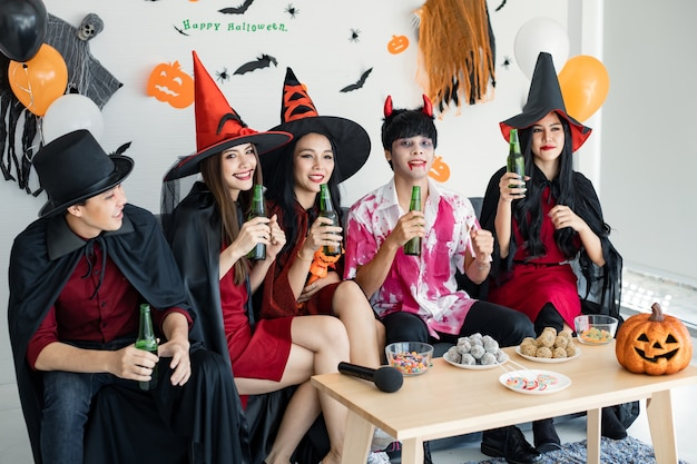 Bende van jonge aziatische in kostuumheks, tovenaar met halloween-feest voor dans en drankje en dronken in de kamer. groep tiener thai met vieren halloween. concept feest halloween thuis.