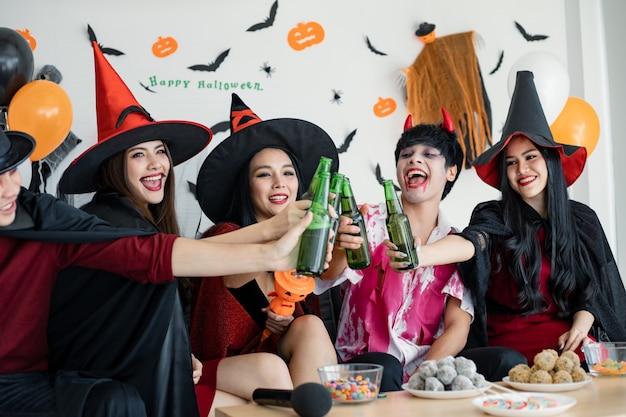 Bende van jonge aziatische in kostuumheks, tovenaar met halloween-feest voor gerinkelfles en drankje in de kamer. groep tiener thai met vieren halloween. concept feest halloween thuis.
