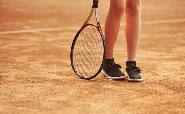 Benen en racket van vrouwelijke speler die overdag in de rechtbank staat.