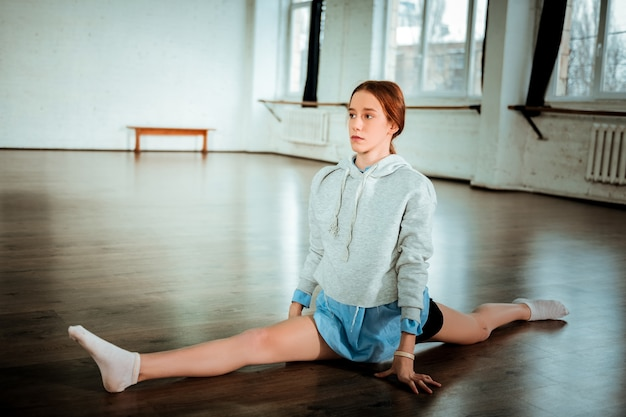 Benen gespleten. mooie donkerharige tiener in zwarte korte broek ziet er serieus uit terwijl hij zijn benen splitst