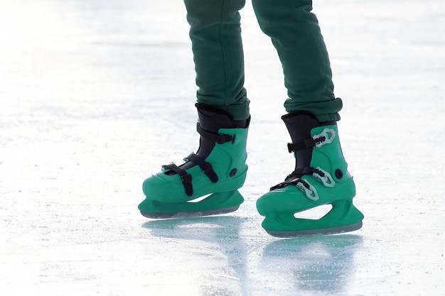 Benen in het blauw schaatsen op de ijsbaan. sporten en amusement. rust- en wintervakanties.