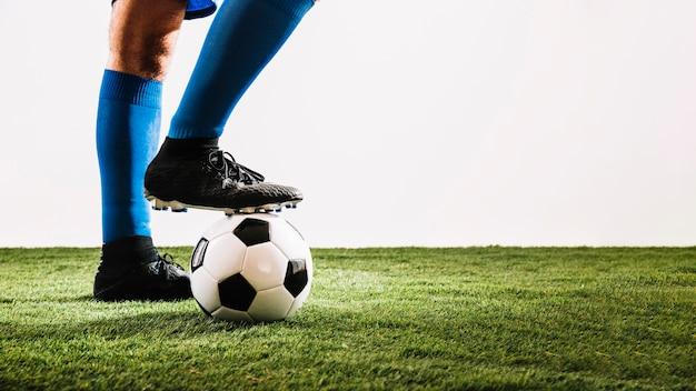 Benen in laarzen die op bal stappen