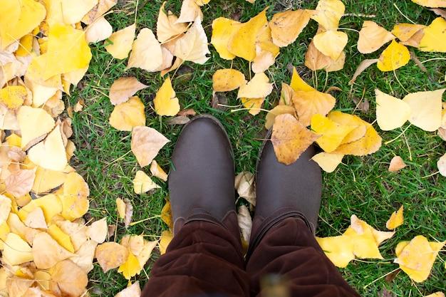Benen in laarzen staan op de grond in park, gras met herfstbladeren, bovenaanzicht