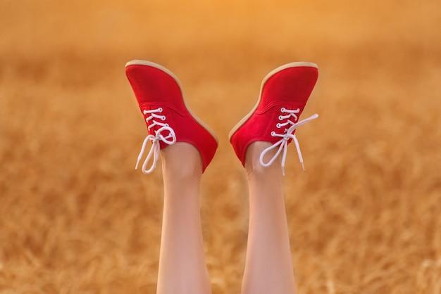 Benen in rode schoenen omhoog opgeheven. vrouw op tarweveld.