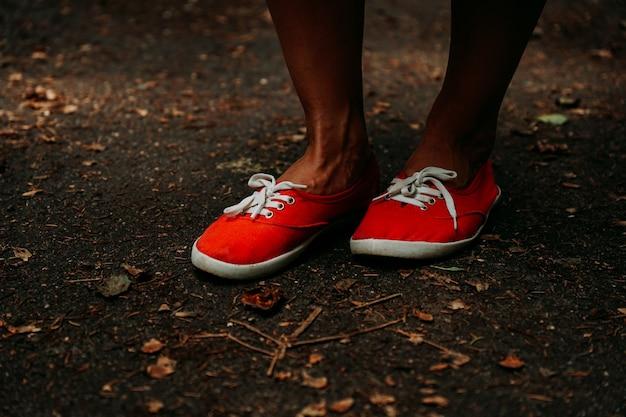 Benen in rode sneakers op een herfstpad in het park. zwart lederen poten. sporten in het zomerbos