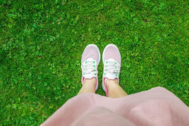Benen in roze sneakers op groen gras.