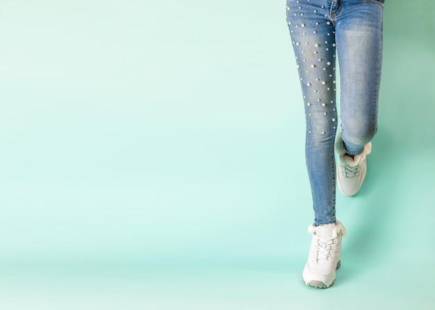 Benen in strakke spijkerbroek en witte wintersneakers tegen de blauwe muur