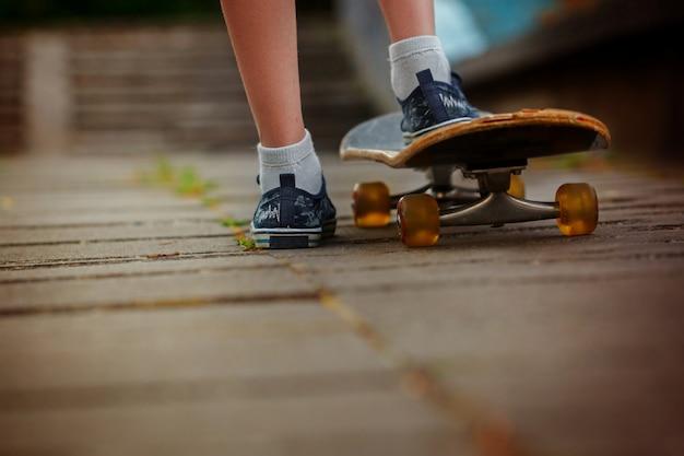 Benen op skateboard dichte omhooggaand op de straat in zonnige dag