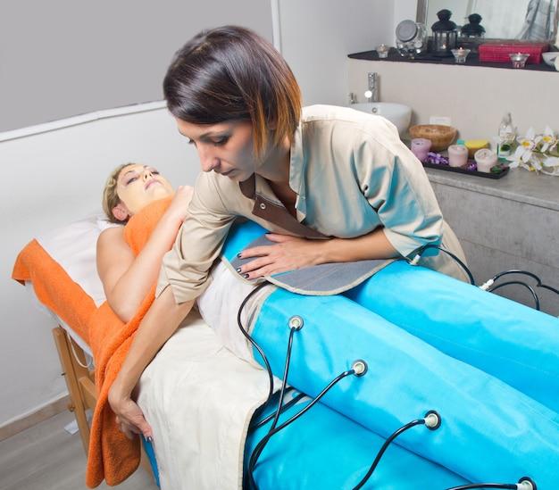 Benen pressotherapy machine op vrouw in schoonheidscentrum