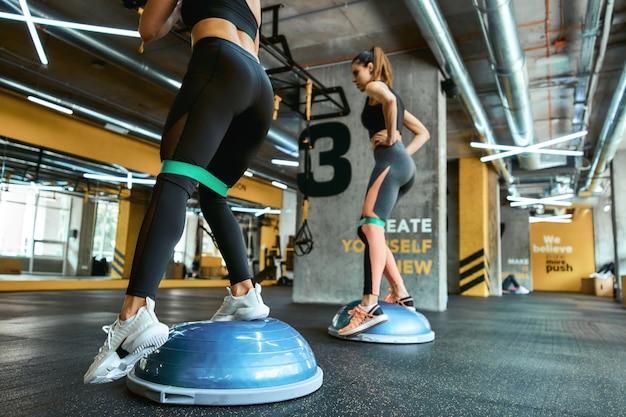 Benen trainen. twee atletische vrouwen in sportkleding trainen met weerstandsfitnessband bij crossfit gym, met behulp van speciale sportuitrusting. training, training, wellness en lichaamsverzorging