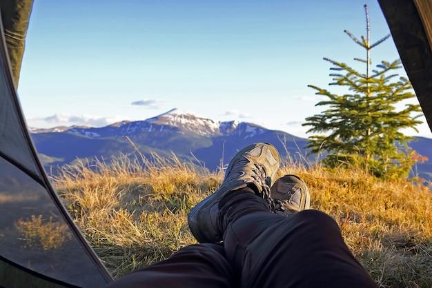 Benen vakantieganger camper in tent met uitzicht op de bergen