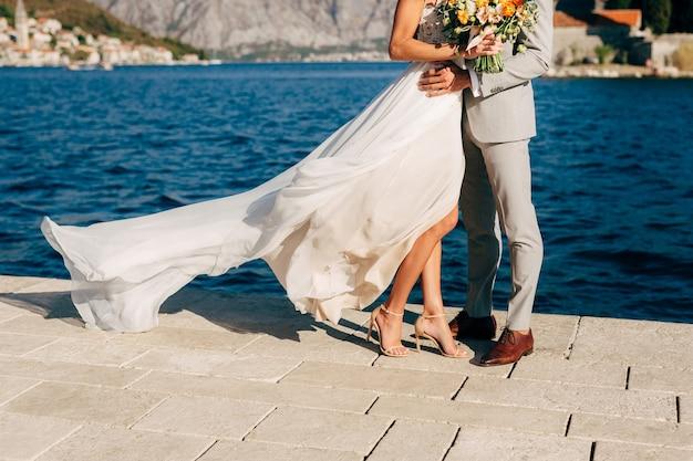Benen van de bruid en bruidegom knuffelen op de pier in de baai van kotor