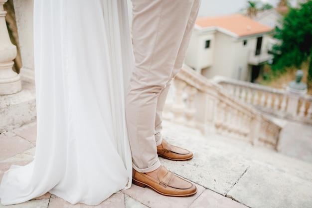 Benen van de bruid en bruidegom knuffelen op de prachtige oude trappen van de tempel