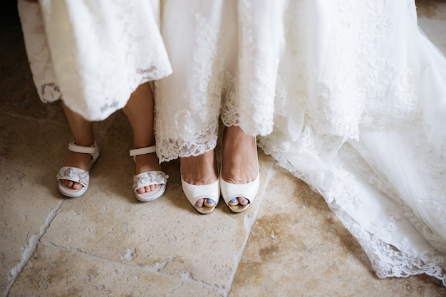 Benen van de bruid in witte schoenen en een klein meisje in sandalen naast haar