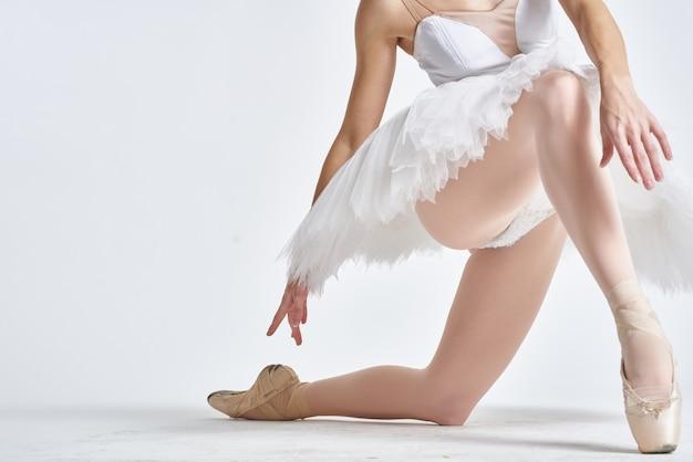 Benen van een ballerina in pointe-schoenen op een licht