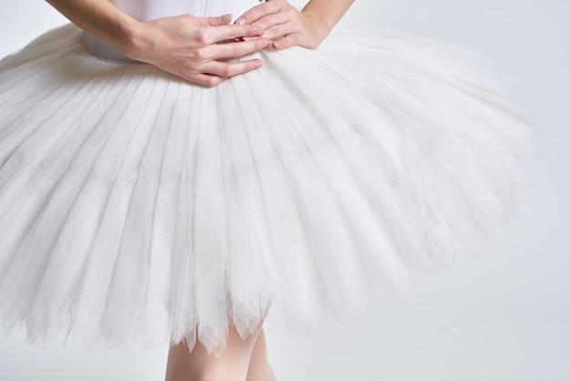 Benen van een ballerina in pointe-schoenen op een lichte achtergrond