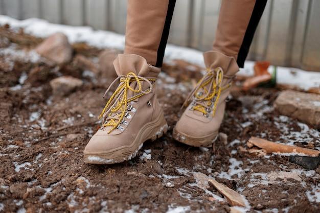 Benen van een jong meisje in modieuze broek met bruine winterlaarzen lopen op de grond. wintercollectie stijlvolle damesschoenen. detailopname.