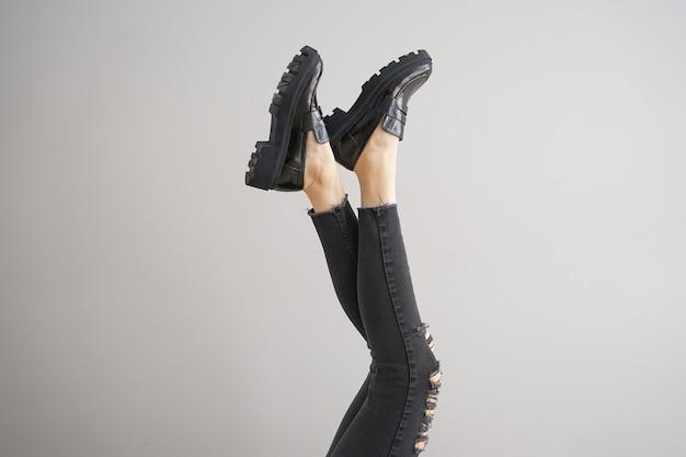 Benen van een jong meisje in spijkerbroek en sneakers op een grijze achtergrond.