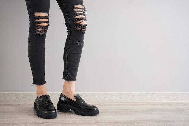 Benen van een jong meisje in zwarte jeans en zwarte schoenen op een grijze achtergrond, ruimte voor tekst.