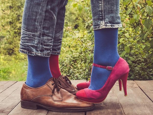 Benen van een jong stel in stijlvolle schoenen en kleurrijke sokken