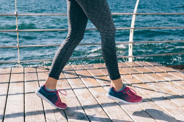 Benen van een jonge atletische vrouw in sneakers tegen de achtergrond van de zee