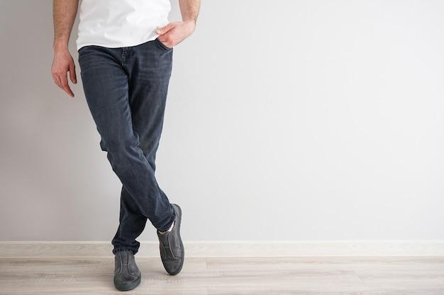 Benen van een jonge man in spijkerbroek en sneakers op een grijze achtergrond.