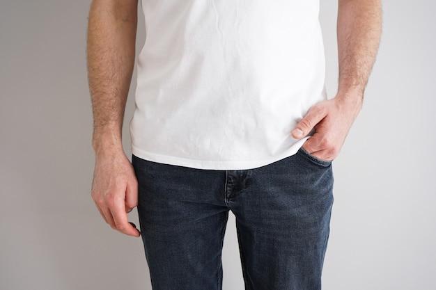 Benen van een jonge man in spijkerbroek met een hand in een zak op grijze muur.
