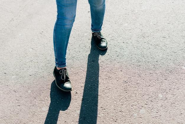 Benen van een jonge vrouw die in spijkerbroek op de weg loopt