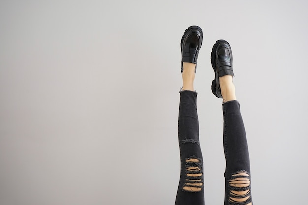 Benen van een jonge vrouw in jeans en schoenen op een grijze achtergrond, plaats voor tekst.