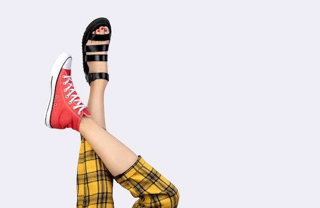 Benen van een jonge vrouw in trendy rode sneakers en sandalen op een grijze ondergrond