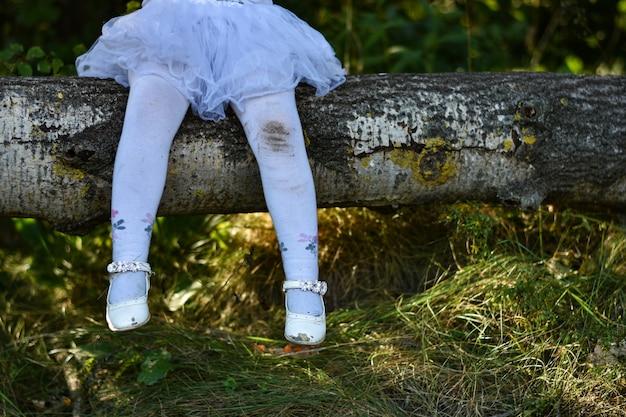 Benen van een klein meisje in een witte jurk en vuile panty in het bos, oude gescheurde schoenen