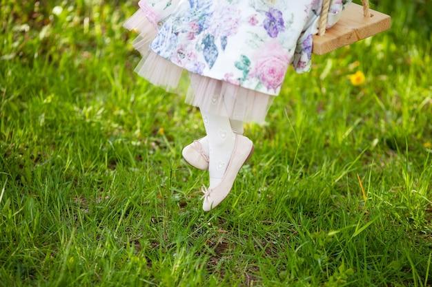 Benen van een klein meisje. plezier hebben in het dorp. details jurken, witte sokken en schoenen. jeugd. zomervakantie. schommel. gelukkig en grappig leven