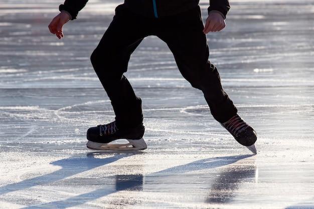Benen van een man die op een ijsbaan schaatst.