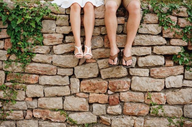Benen van een man en een vrouw die naast elkaar op de stenen omheining zitten