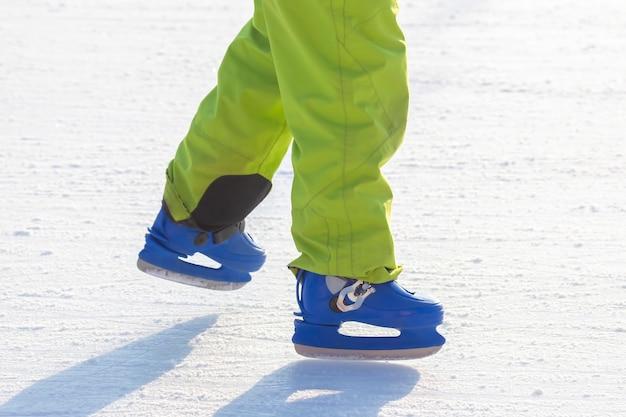 Benen van een man in blauwe schaatsen rijdt op een ijsbaan. hobby's en vrije tijd. wintersport